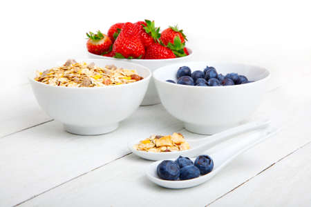 corn flakes: fresh blueberry, strawberry and corn flakes in white porcelain bowl, wooden table