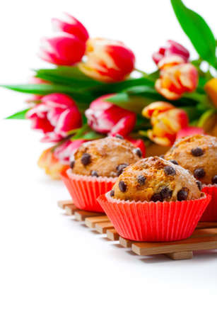 Muffins with tulips isolated on white background photo