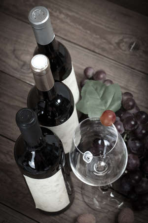red wine bottle: red grapes with wine bottles on brown background