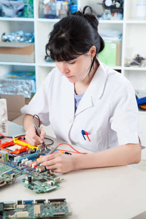 Girl debugging an electronic precision device Stock Photo - 18495010