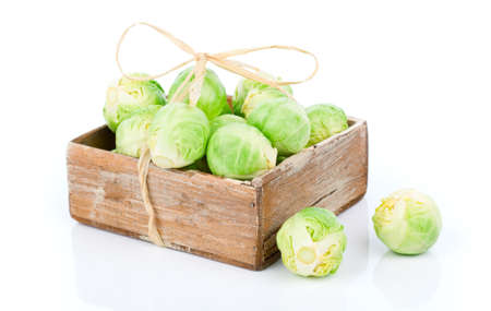 tightly: fresh green brussels sprouts in the wooden box, on a white background Stock Photo