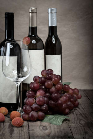 red grapes with wine bottles on wooden background photo