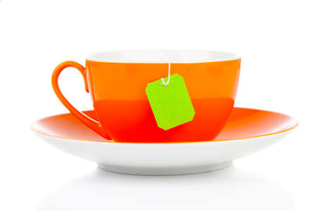 orange tea cup and green tea bag. Isolated on white background photo