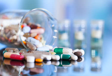 Colorful tablets with capsules and pills on blue background 写真素材