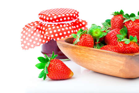 Strawberry berries in a wooden bowl with a jar of jam isolated on white background photo