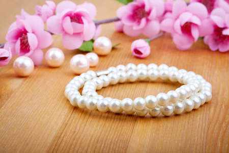 artificial flower: pearl bangles, with pink flower on wooden background Stock Photo