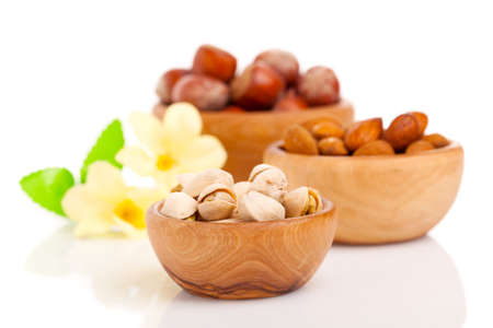 pistachios: Nuts in a wooden bowl on a white background