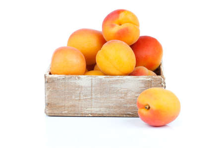 ripe apricots in wooden box, Isolated on white backgroun photo