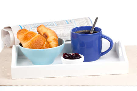 Fresh coffee and tasty croissant in a tray for breakfast. with newspaper, on white background photo