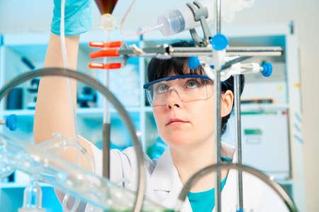 Wetenschappelijk onderzoeker die een vloeibare oplossing in een lab Stockfoto - 21541613