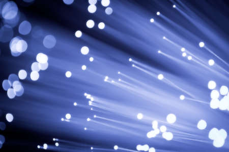 Close up on the ends of a selection of illuminated blue fiber optic light strands with black background. photo