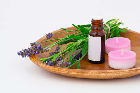 Aromatherapy Lavender oil and lavender flower in the wooden bowl, isolated on white background photo