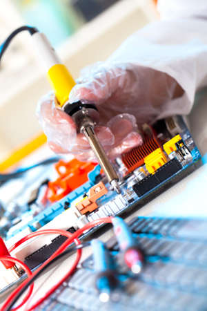 soldering electronic parts on a printed circuit board photo
