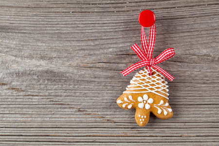 Gingerbread cookie hanging on wooden background. Christmas decoration. photo