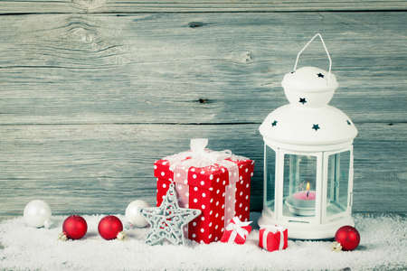Burning lantern in the snow with christmas decoration, on wood background, photo