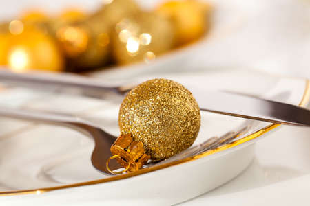 silver cutlery decorated with a golden Christmas bauble photo