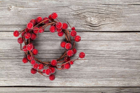 Christmas wreath from red berries on wooden background Stock Photo