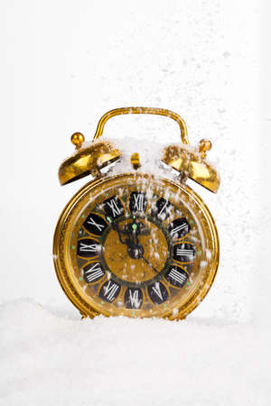 Antique gold clock in the snow. with copy space on a white background photo