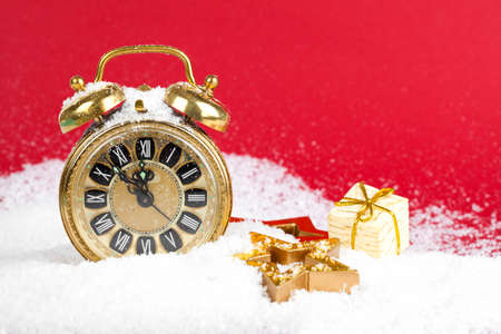vintage christmas decoration golden star and antique golden clock in snow on red background photo