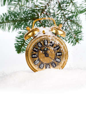 vintage christmas decoration - antique golden clock and fir-tree in snow  with copy space, on white background photo