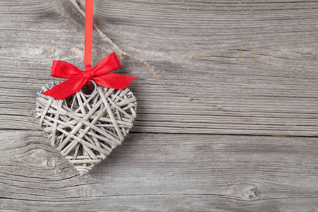 one heart with red bow, on wooden background photo