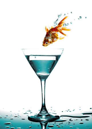 saut de poissons d'or � un verre � martini, fond blanc photo