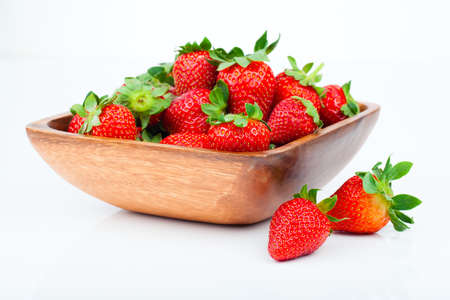 strawberry plant: strawberry berry in wooden bowl, isolated on white  Stock Photo