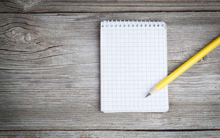 lapiz: Bloc de notas en una mesa de madera con un lápiz Foto de archivo