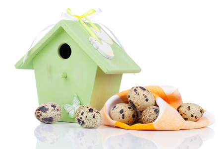 quail eggs with birdhouse, on a white background photo