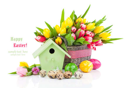 Easter eggs with tulips flowers and birdhouse, on a white background photo