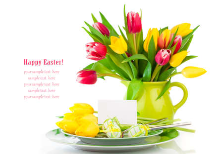 Easter eggs and blank for text in a plate, with tulips flowers on a white background photo