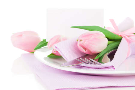Romantic dinner  table setting with roses tulips and cutlery, with and blank for text on a white background. Copy space. photo