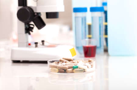 Science lab research safe of new drugs, microscope and red pills