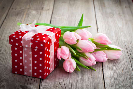 beautiful tulips with red polka-dot gift box. happy mothers day, romantic still life, fresh flowers. on wooden background photo