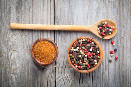 flavorings: Colored Pepper in the wooden bowl, on wooden board