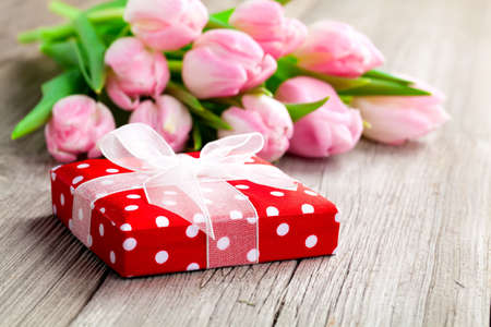 beautiful tulips with red polka-dot gift box  happy mothers day, romantic still life, fresh flowers  on wooden table  photo