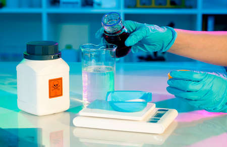 hazardous: researchers work in modern scientific lab  Preparation of hazardous solution