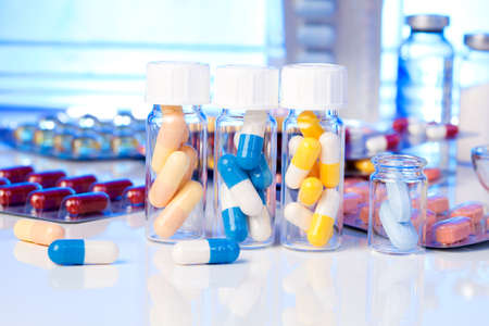 pills bottle: Colorful medical capsules in bottle, on white background.