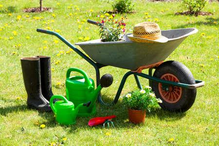 carretilla: Herramientas de jardinería y un sombrero de paja sobre el césped en el jardín