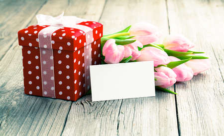 beautiful tulips with red polka-dot gift box  happy mothers day, romantic still life, fresh flowers  on wooden background photo