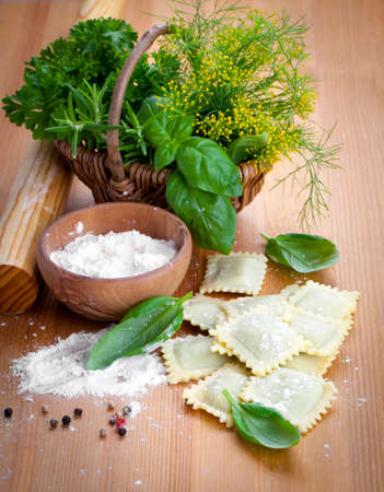 homemade style: Homemade pasta ravioli with fresh basil, on wooden background