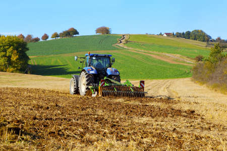 farm tractor on the field working, plowing land photo