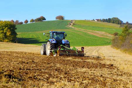 landbouwtractor op het werkveld, ploegen land Stockfoto