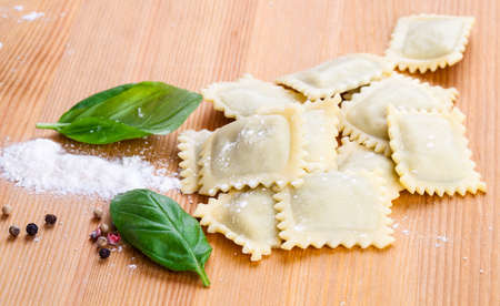 perle: Homemade pasta ravioli with fresh basil, on wooden background
