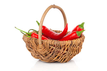 Red chili pepper in a wicker basket, isolated on white background photo