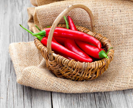 Red chili pepper in a wicker basket with burlap on the wooden background photo