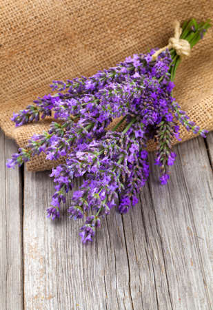 lavender flowers in a basket with burlap on the wooden background photo