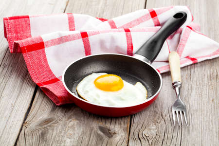 Fried egg in a frying pan, on an old wooden table Standard-Bild