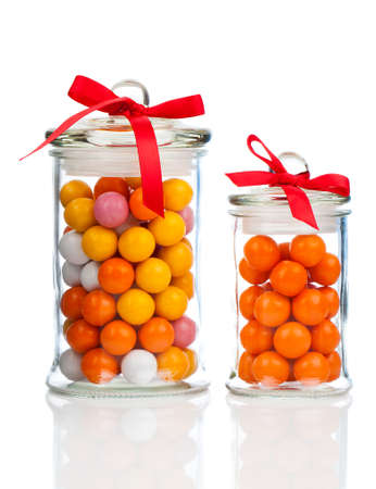 gumballs: Colorful background of assorted Gumballs in  glass jar,  isolated over white background