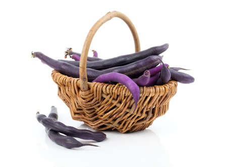 Red bean pods in wicker basket over white background photo